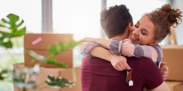 Couple hugging after buying a new house
