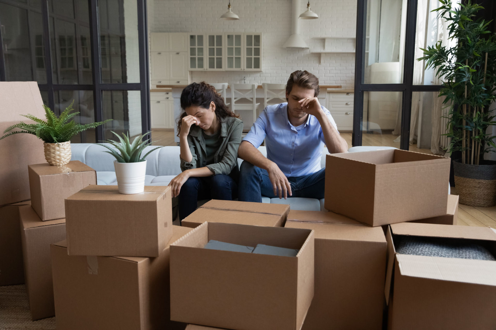 Tired unhappy young Caucasian couple sit on sofa in new living room feel unmotivated unpacking. Upset stressed millennial man and woman have fight quarrel unboxing packages relocating moving.